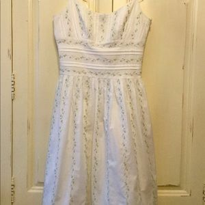 White dress with floral embroidery.